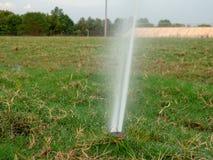 Nära sikt av denmalde spridaren som besprutar ett okammat fält som skräpas ner med dött gräs fotografering för bildbyråer