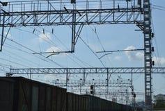 Nära sikt av det elektriska kontaktnätverket av järnvägar och järnvägar i bakgrunden arkivbilder