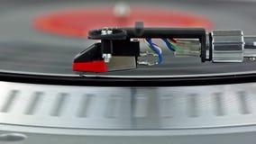 Nära sikt av ett rekord som spelar på en skivtallrik arkivfilmer