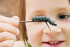 Nära sikt av flickan med larven för påfågelfjäril arkivfoto