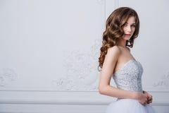 Nära stående av den härliga le brudkvinnan med långt lockigt hår som poserar i bröllopsklänning på inre och att le Arkivbilder