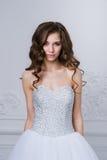 Nära stående av den härliga le brudkvinnan med långt lockigt hår som poserar i bröllopsklänning på inre och att le Royaltyfri Bild