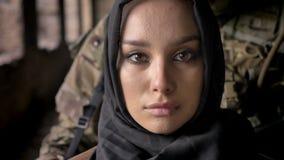 Nära stående av den unga muslimkvinnan i hijab som ser kameran, beväpnad soldat med vapenanseende bak kvinna, militär arkivfilmer