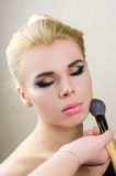 Nära stående av en ung flicka med ljust smink på en ljus bakgrund med en borste för makeup Royaltyfria Foton