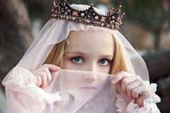 Nära stående av flickatjuserskan i kronan med en framsida som täckas med en skyla och charmiga stora ögon royaltyfri fotografi