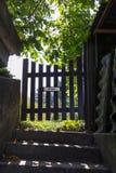 Nära staket under träd och solljus Arkivfoton