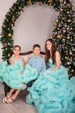Nära trädet för det nya året sitter modern med hennes son och dotter i eleganta blåa klänningar på en fotoperiod i studion fotografering för bildbyråer