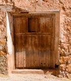 nära upp av en gammal trästängd dörr med ett öppnat litet fönster i en vägg av betong, gyttja och stenen i ett stängt övergett hu royaltyfria foton