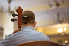 nära upp av en man som spelar violoncellen, en verklig konsert, bakre sikt arkivbild