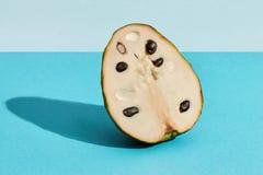 Nära upp högkvalitativ bild av halvan av socker-Apple, frukt av Annonasquamosacherimoyaen, fruktsammansättning på blå pastell royaltyfria bilder