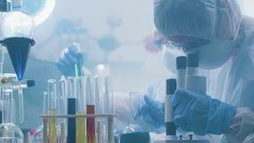 Nära upp handheld skott av kemister som arbetar i ett laboratorium som fylls med dunster eller rök stock video