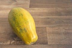 Nära upp hel papaya på träbakgrund royaltyfria bilder