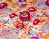 Nära upp isolerat foto av en tomat-, bacon- och chilipizza royaltyfria bilder