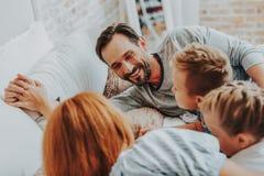 Nära upp lycklig fader med hans familj i säng arkivfoton