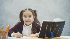 Nära upp smart skolflicka på en grå bakgrund Under denna tid sitter han på tabellen Skriver försiktigt läxa stock video