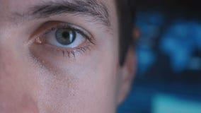 Närbildöga i makro av en manlig programmerare Geek i en datorhall som fylls med bildskärmskärmar arkivfilmer