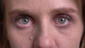 Närbildöga-stående av den gulliga blonda modellen som uppmärksamt och fast håller ögonen på in i kamera på svart bakgrund arkivfilmer