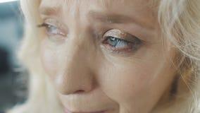Närbildögon av den ledsna gamla kvinnan Kvinnan gråter stock video