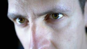 Närbild av ögonen och framsidan av en ung man som arbetar på en dator på en svart bakgrund stock video