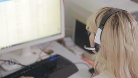 Närbild av affärskvinnan som talar på hörlurar med mikrofon i en appellmitt lager videofilmer
