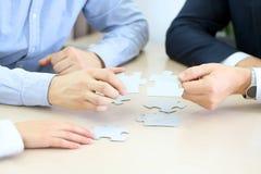 Närbild av affärsmanhandförbindande pusslet Arkivbild