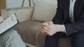Närbild av affärsmannen som flyttar nervöst händer medan övergående psykologiskt prov under besök till den kvinnliga psykoanalyti stock video