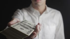 Närbild av affärsmannen som ger en trumma av dollarräkningar Begreppet av timpenningar välgörenhet stock video
