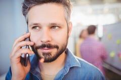 Närbild av affärsmannen som lyssnar till mobiltelefonen på det idérika kontoret arkivbild