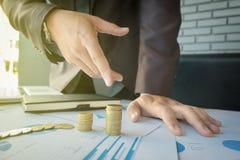 Närbild av affärsmannen som pekar myntet till den stigande bunten av mynt Fotografering för Bildbyråer