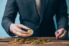Närbild av affärsmannen som räknar och rymmer bitcointecknet av mynt - indikera finansiell handelrikedom och affär för cryptocurr Royaltyfria Foton