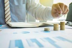 Närbild av affärsmannen som sätter myntet till den stigande bunten av mynt Royaltyfria Foton