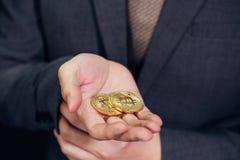 Närbild av affärsmanvisningen och hållande bitcointecken av myntet Arkivbilder
