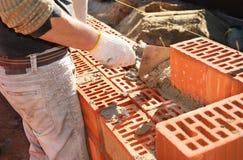 Närbild av arbete för konstruktionsprocessmurare med tegelsteninstallation vid murslevspackeln utomhus Royaltyfri Foto