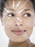 Närbild av att le affärskvinnan med binära siffror och piltecken som flyttar sig in mot hennes öga mot vit bakgrund royaltyfri foto