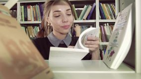 Närbild av att le den kvinnliga studenten som väljer ett passande från bokhyllan lager videofilmer