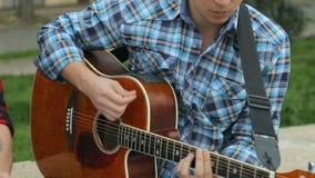 Närbild av av en gitarr som spelar på gatan arkivfilmer