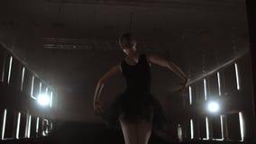 Närbild av balettdansören som henne övningsövningar på mörk etapp eller studio Ballerina visar klassisk balettpas l?ngsamt stock video