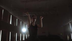 Närbild av balettdansören som henne övningsövningar på mörk etapp eller studio Ballerina visar klassisk balettpas l?ngsamt arkivfilmer