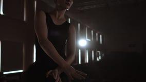 Närbild av balettdansören som henne övningsövningar på mörk etapp eller studio Ballerina visar klassisk balettpas l?ngsamt lager videofilmer