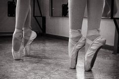 Närbild av ballerinafot på pointeskor i dansstället Tappningfotografi Närbild av en ballerina i dansstället arkivfoto