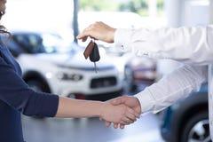 Närbild av bilåterförsäljaren som skakar handen för köpare` s och ger tangentafte royaltyfri bild