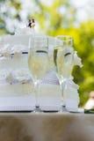 Närbild av bröllopstårta- och champagneflöjter Arkivfoto