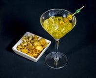 Närbild av coctailen martini med oliv på tabellen mot royaltyfri fotografi