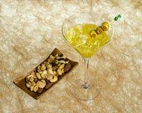 Närbild av coctailen martini med oliv på tabellen mot royaltyfria bilder
