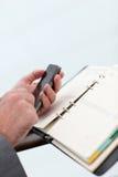 Närbild av dagordningen och smartphonen Arkivbilder