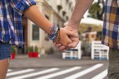 Närbild av de hållande händerna av ett ungt par i en sommarstad romantiker Arkivfoto