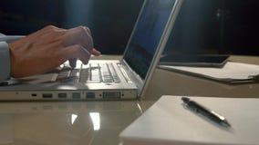 Närbild av denöverkant datoren och en manmaskinskrivning något på den arkivfilmer