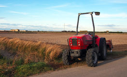 Närbild av den åkerbruka röda traktoren som odlar fältet över blå himmel Royaltyfri Bild