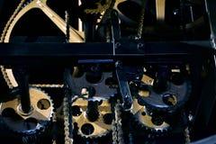 Närbild av den öppna mekanismen av en tappningklocka med guld- kugghjulhjul och kedjor royaltyfri fotografi