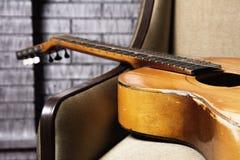 Närbild av den akustiska gitarren som ligger på soffan royaltyfri foto